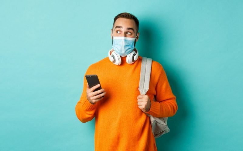 Young man in face mask using mobile phone, holding backpack, staring left amazed, standing against light blue background.